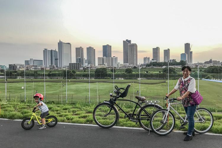 叶大と奥さんのお母様と多摩川河原サイクリングコースで武蔵小杉のビル群を背景に記念撮影